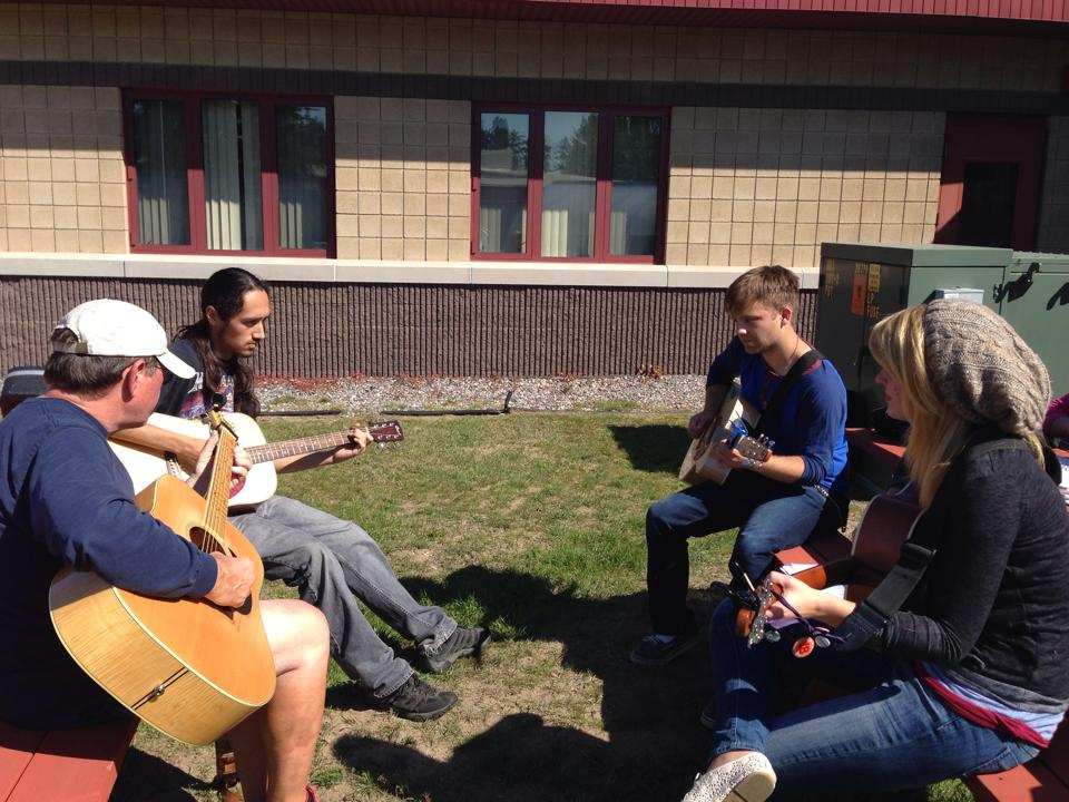 A picture of students playing guitars outside at BMCC.